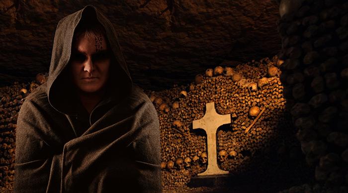Praying monk in the dark Paris catacombs