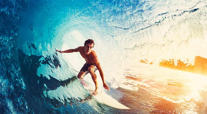Surfer on blue ocean wave getting barreled in Kauai